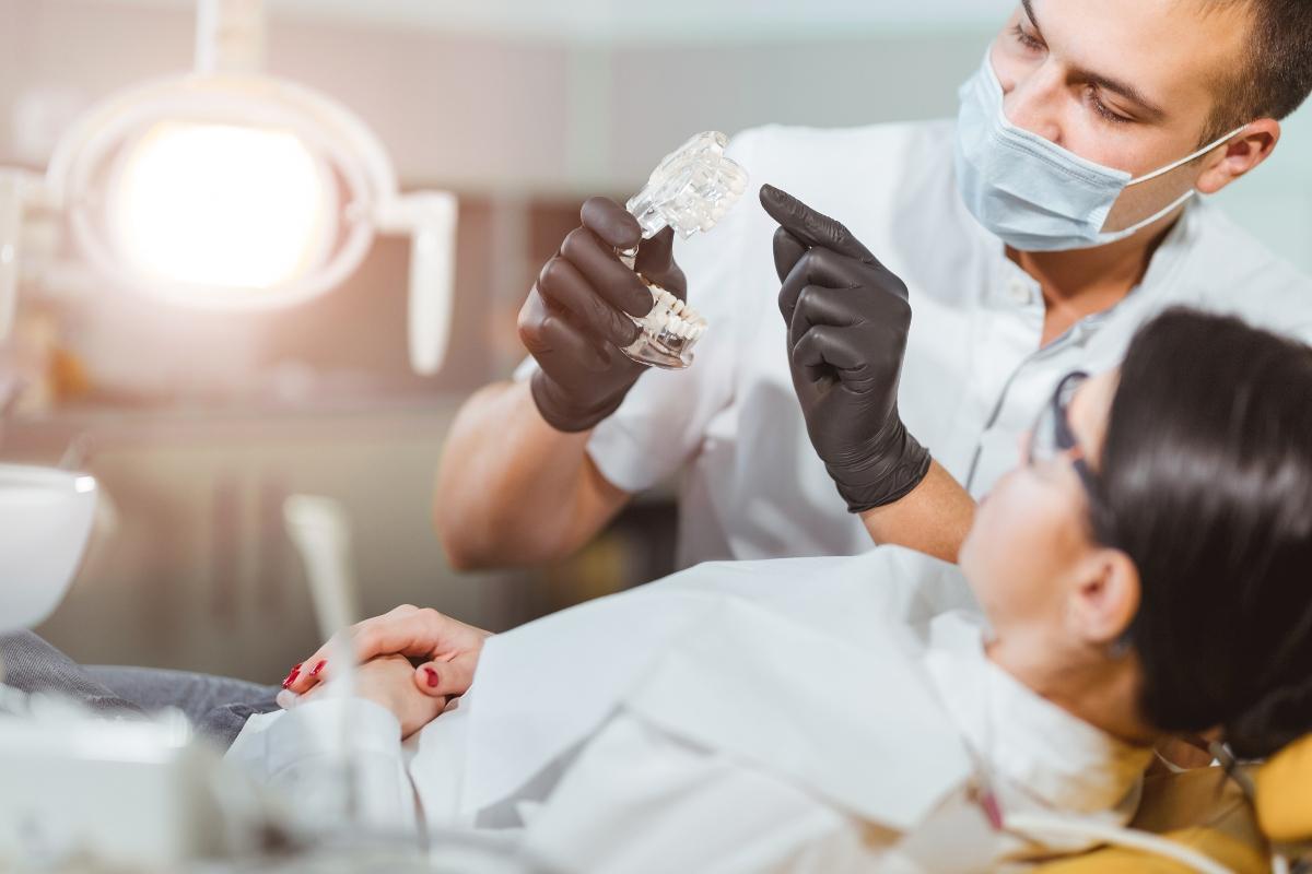 dentist holding dental implant model